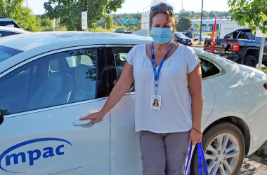 Woman wearing surgical mask standing beside MPAC vehicle